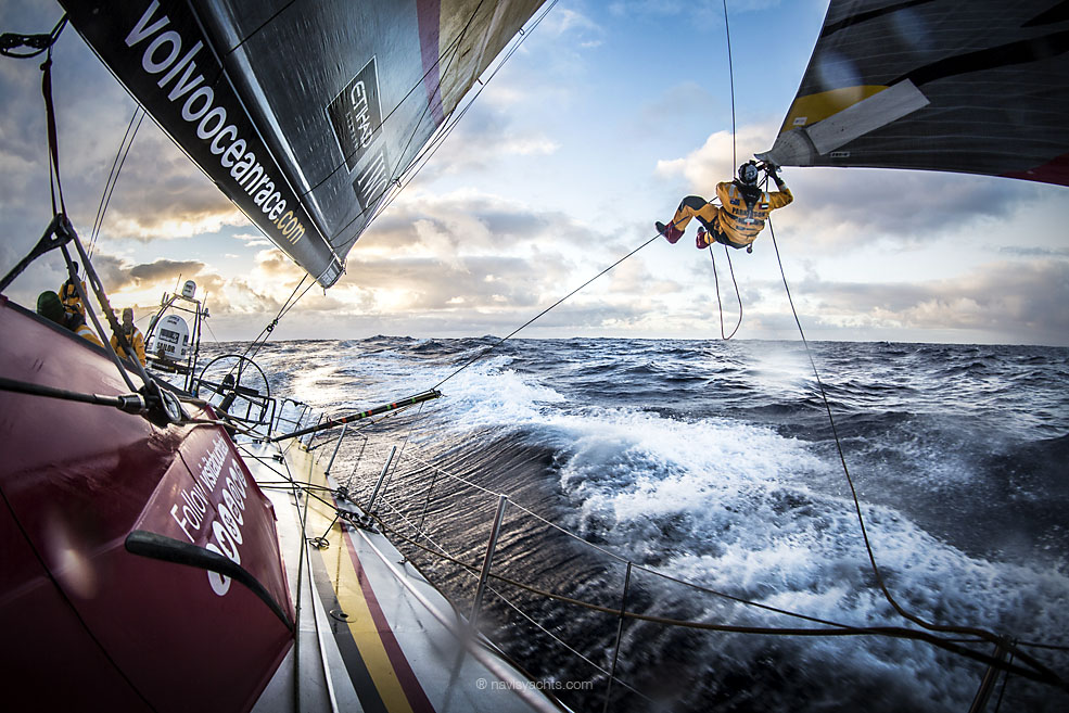 """March 23, 2015. Leg 5 to Itajai onboard Abu Dhabi Ocean Racing. Day 05. Luke """"Parko"""" Parkinson swings out over the southern ocean to tie a changing sheet on the FRO at sunset."""